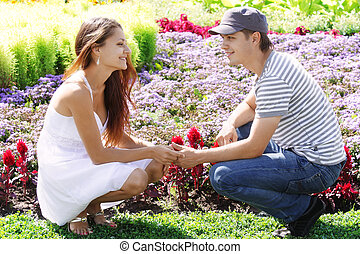 Couple squatted down at flower-bed