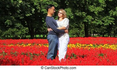 couple stand in park in flowers talk and smile