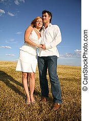 couple stand on meadow