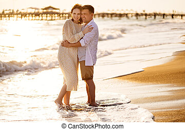 a couple, husband and wife stand on the shore line, sandy beach. a romantic relationship and travel together.