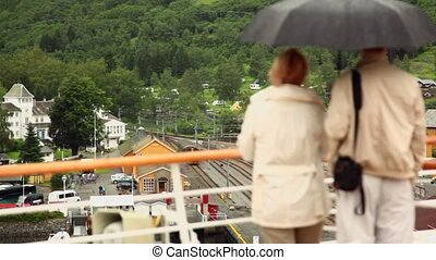 Couple stand under umbrella and watch at railroad station in...