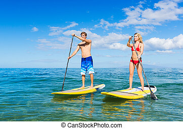 Couple Stand Up Paddling in Hawaii - Attractive Couple Stand...