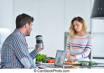Couple standing and sitting at the kitchen while smiling and man reading a newspaper and holding mug before work.