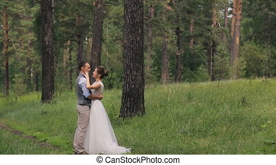 Couple standing arm in arm at wedding photo shoot in woods outdoors