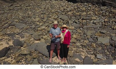 Couple standing at wild beach with cliffs behind, Portugal -...