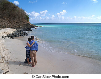 Couple standing on Frys beach on Antigua Barbuda in the Caribbean Lesser Antilles West Indies.