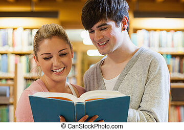 Couple standing holding a book in the library