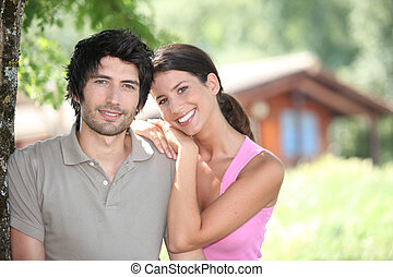 Couple standing in front of a holiday cabin