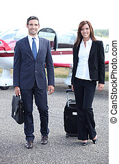 Couple standing in front of a light aircraft