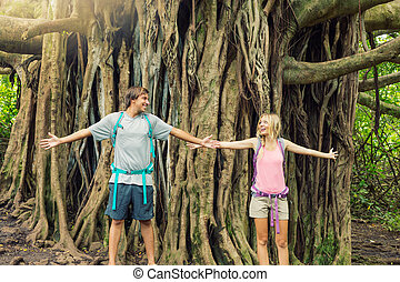 Couple standing in front of incredible banyan tree