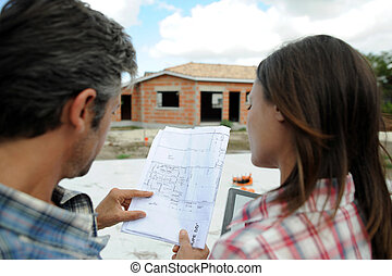 Couple standing in front of their future home