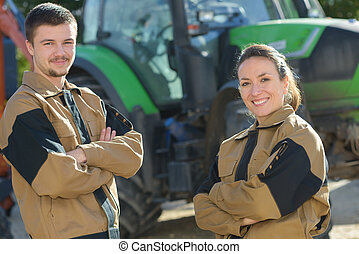 couple standing in front of tractor