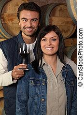 Couple standing in front of wine barrels