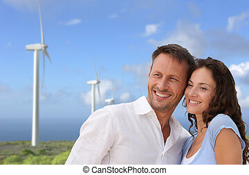 Couple standing in front of wine turbines