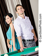 Couple standing near billiard table
