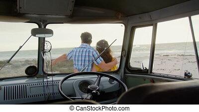Couple standing near camper van on the beach 4k