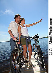 Couple standing on a bridge with bicycles