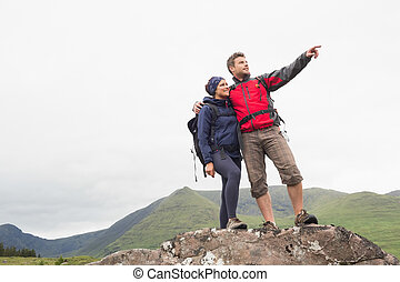 Couple standing on a rock looking