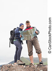 Couple standing on a rock reading map