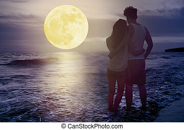 couple standing on beach and watching the moon. Celebrate Mid autumn festival together