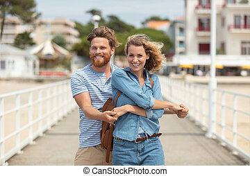 couple standing on beach pier embracing