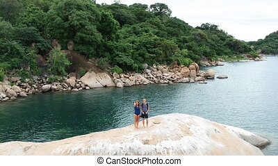 Couple Standing on Large Rock of Lake Malawi with Woman Waving