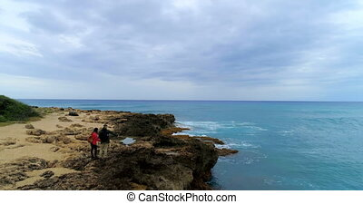 Couple standing on the rocky sea coast 4k - Carefree couple...