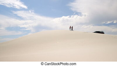 Couple standing on the sand dune in desert 4k - Couple...