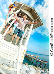 couple standing on tower on the beach with beautiful flowers bouquet