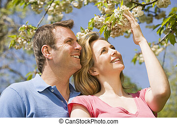 Couple standing outdoors holding blossom smiling