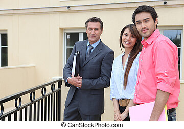 Couple standing outside a house with an estate agent