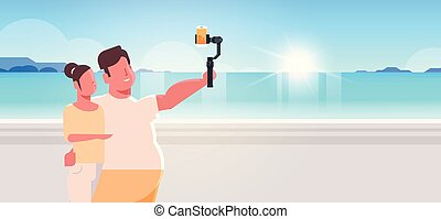 couple standing together sea beach obese man with thin woman holding selfie stick taking photo on smartphone camera summer vacation concept seaside landscape portrait horizontal
