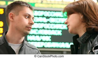 couple stands against indicator board in railroad station and talks