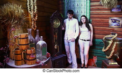 couple stands and talk in ancient wooden house near big clock