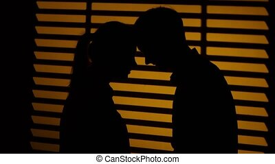 Couple stands by and perched their heads to each other. Silhouette. Close up
