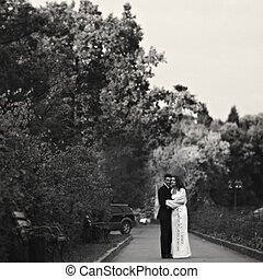 Couple stands on the path in the park