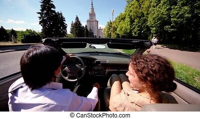 Couple start moves in cabriolet on road at day - Couple...