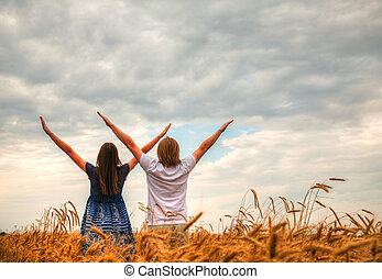 Couple staying with raised hands at a wheat field at sunset ...