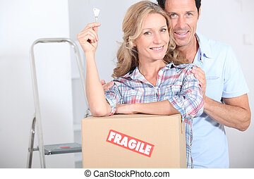 Couple stood by packing boxes