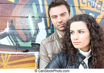 Couple stood by wall covered in graffiti