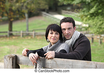 Couple stood by wooden fence