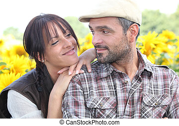 Couple stood in field of flowers