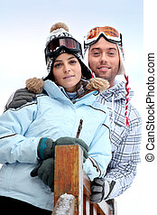 Couple stood in front of skiing holiday accommodation
