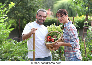 Couple stood in garden with vegetables