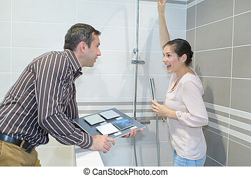 couple stood in shower cubicle exhibit holding tile samples
