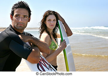 Couple stood on beach ready to surf