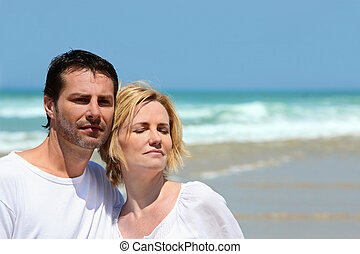 Couple stood together on a  beach