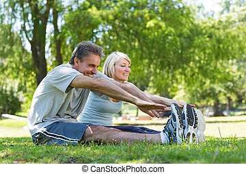 Couple stretching in the park - Happy couple stretching ...