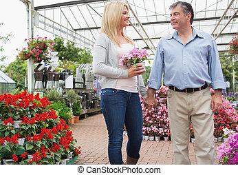 Couple strolling through garden center - Couple strolling...