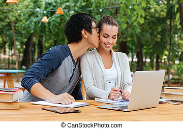 Couple studying and kissing in outdoor cafe